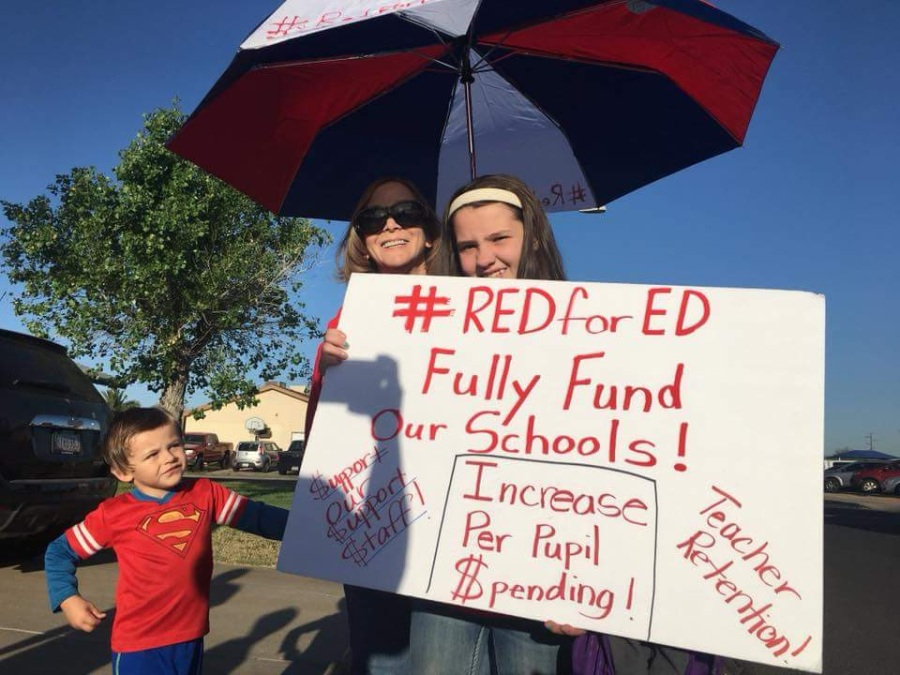 family with a protest sign saying Red for Ed Fully Fund Our Schools