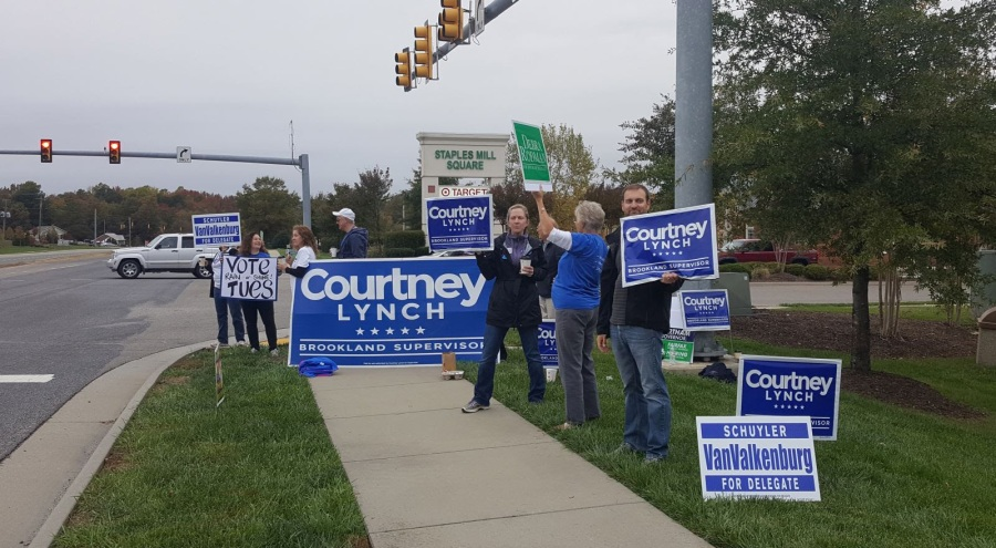 volunteers at an intersection holding signs saying Courtney Lynch Brookland Supervisor