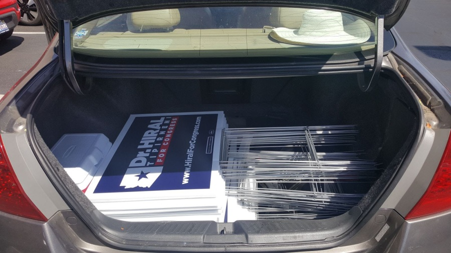 trunk full of yard signs saying Dr. Hiral Tipirneni for Congress